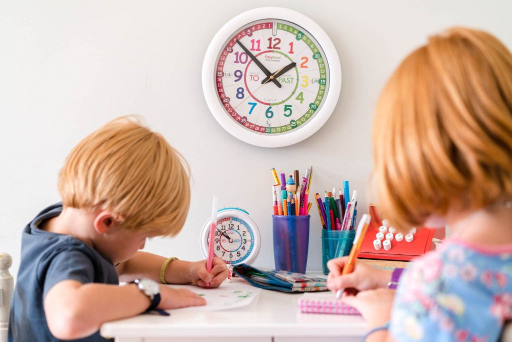 Two Children learning how to tell the time with an EasyRead Time Teacher Wall Clock